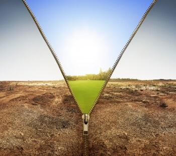 Hinter einer dürren Wüstenlandschaft eröffnet sich eine saftig grüne Landschaft