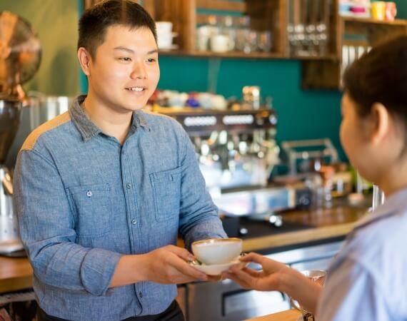 Das Bild zeigt einen Jungen, der einer Kundin einen Kaffee überreicht.