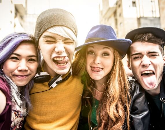 Vier Jugendliche posieren lustig in die Kamera