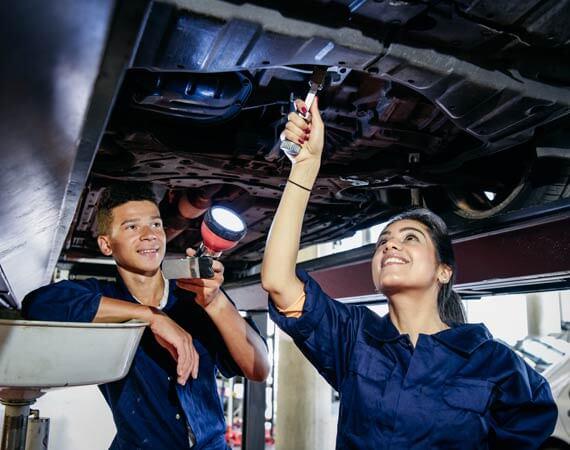 Zwei Jugendliche in einer Auto-Werkstätte mit Mechaniker-Kleidung reparieren und durchleuchten den Unterboden eines Autos
